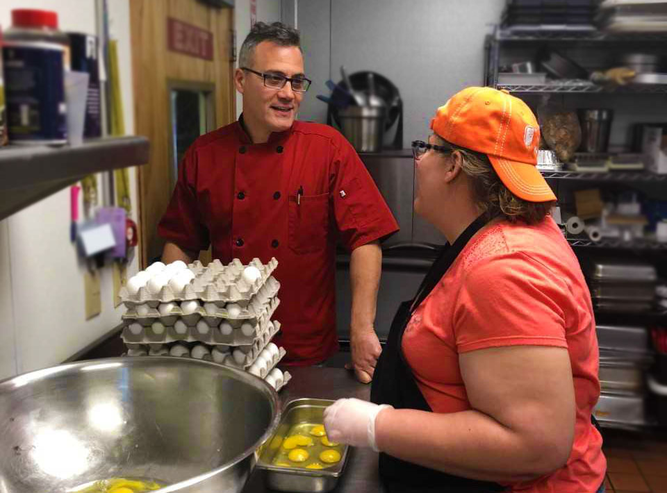 A man and woman talk inside of a kitchen where eggs are being prepared