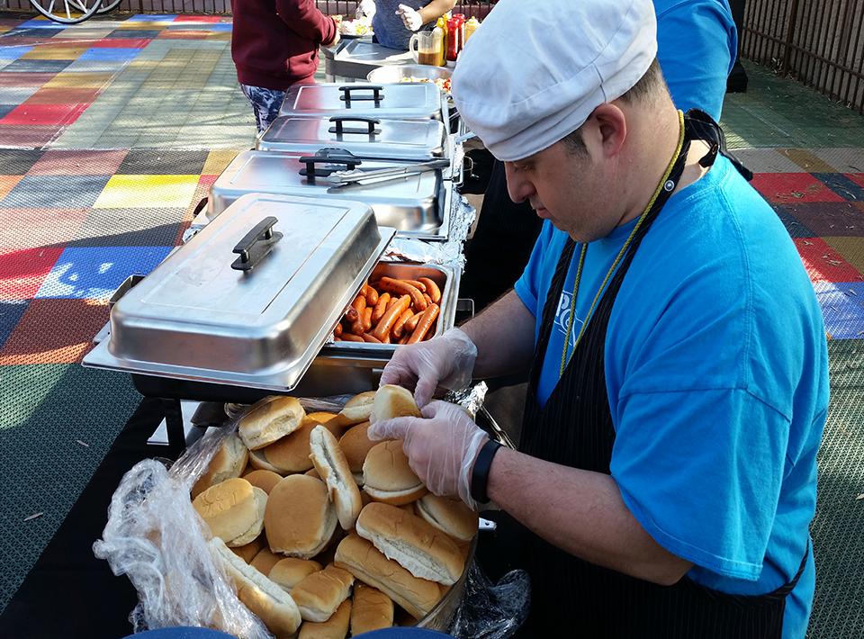 A man preparing hotdog and hamburger buns at an outdoor picnic.